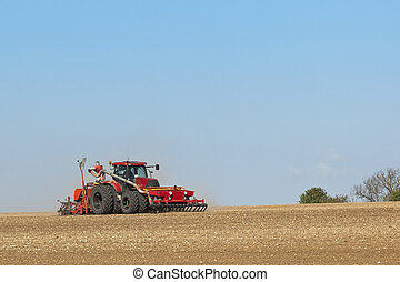 sowing crops 2 - a red tractor sowing crops in a chalky...