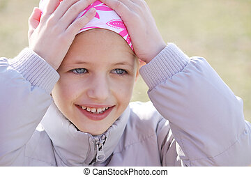 Child with cancer - child wearing head scarf due to hair los...