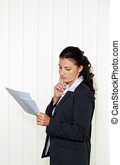 Businesswoman reading a letter in the office. Message from...