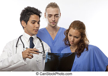 three medical studentsinternsnurses looking at an x-ray