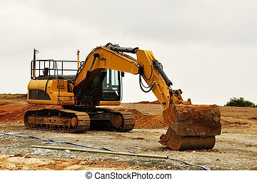 Excavator in red soil - Yellow excavator in red soil and...