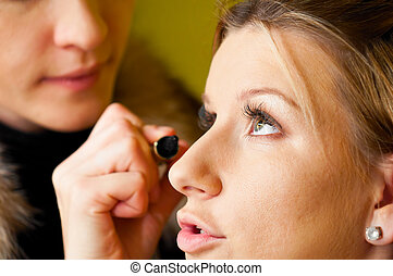 doing make-up - makeup artist is applying cosmetics on model...