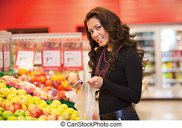 Portrait of a young woman buying fruits