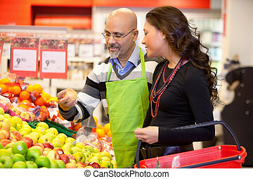 Grocer and Customer - Shop assistant holding apple with...