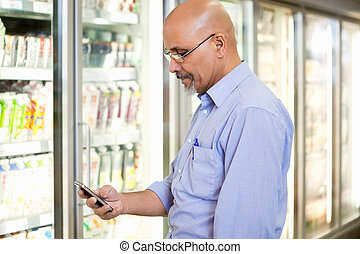Cell Phone Grocery List - Smiling mature man looking at...