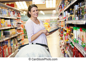 Mother with Electronic Shopping List - Woman holding digital...