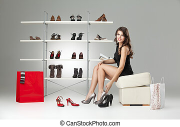 young woman sitting trying shoes looking happy