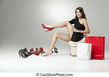 young woman sitting trying on shoes looking happy