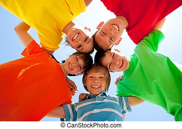 Siblings in a circle - Five smiling siblings arm in arm in a...