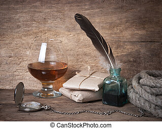 quill in the inkwell and glass of wine