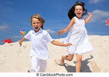 Happy children on beach - Happy young brother and sister...
