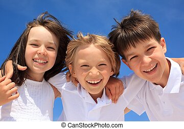 Happy children - Happy young girl embracing two bothers in...