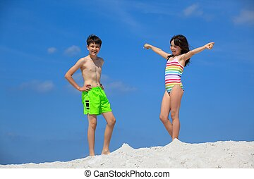 Kids in bathing suits on beach - A boy and girl wearing...