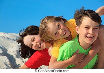 Children playing on beach - Closeup of three young children...