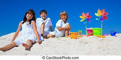Children and pinwheels on sand - Three children leaping and...