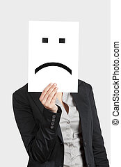 Sad Face - Woman showing a blank paper with a sad emoticon...