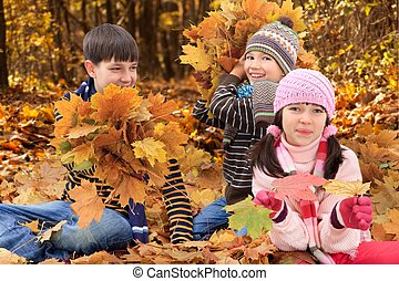 Children playing in Autumn - Happy sister and two young...