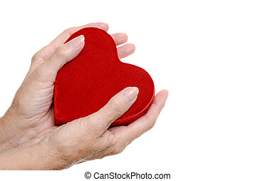 elderly woman hands holding a heart - isolated elderly woman...