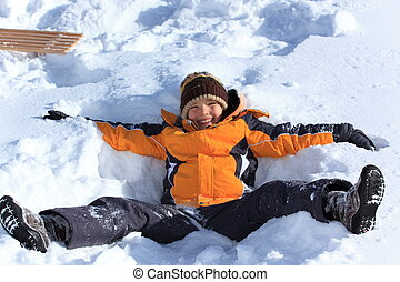 Boy playing in snow - Closeup of happy young boy lying on...