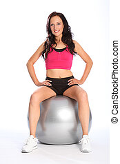 Beautiful smiling woman sitting on exercise ball