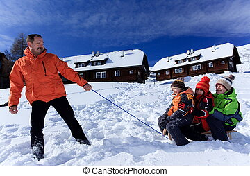 Father pulling kids on sledge