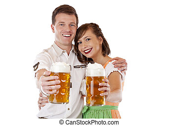 Young man and woman in dirndl holding oktoberfest beer stein...