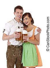 Young Bavarian couple in love with Oktoberfest stein...