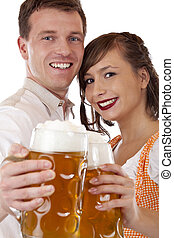 Close-up of a happy Bavarian couple with beer stein.Isolated...
