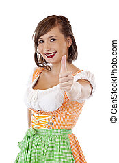 Happy Bavarian woman in Oktoberfest dirndl shows thumb up