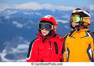 Kids on mountaintop snow - Smiling young boy and girl in ski...