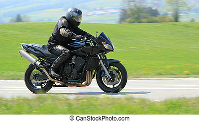 Black biker - Biker wearing black clothes and driving a big...