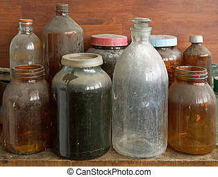 Old dusty glass bottles and jars
