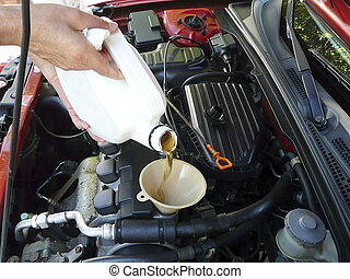 Pouring Motor Oil - Male adding oil with a funnel after a...