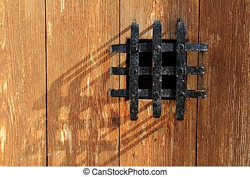 ancient window black metal jail grid wooden door