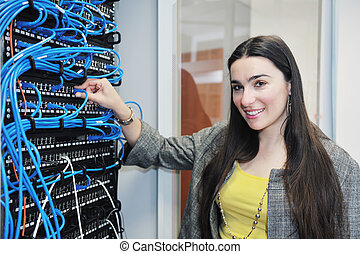 woman it engineer in network server room solving problems...