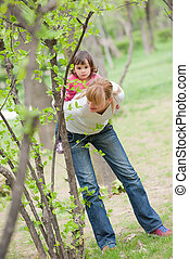 young mother piggybacking her daughter in park