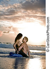 Beach passion - Young sexy couple on beach with sun rising...