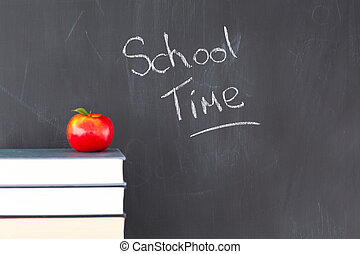 Stack of books with a red apple and a blackboard with...