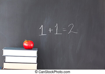 Stack of books with a red apple and a blackboard with 1+1=2...