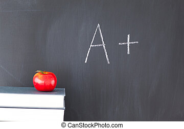 Stack of books with a red apple and a blackboard