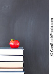 Stack of books with a red apple and a clean blackboard -...