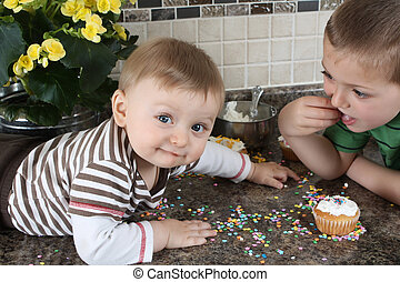 Kitchen fun - Brothers on kitchen counter eating icing sugar