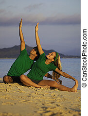 young couple doing yoga, stretches, and meditation on the...