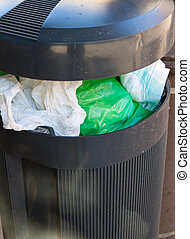 Trash cans with plastic trash - A waste basket with plastic...