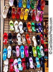 Many colorful shoes in the window of a shoe store