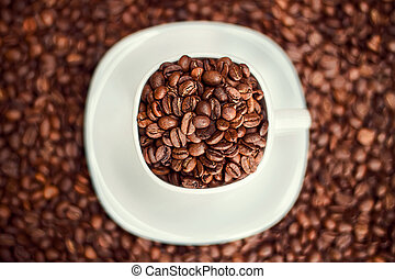 White cup filled with coffee beans