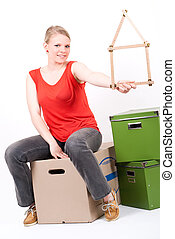 young woman with a house symbol sits on moving box - a young...