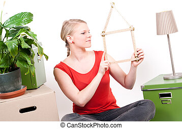 young woman with house symbol sits between move cardboards...