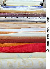 fashion fabric rolls in retail market shop in a row