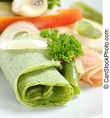 Rolled thin green colored pancake (colored with spinach in...